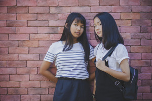 face of two asian teenager standing and looking to camera with eye contact