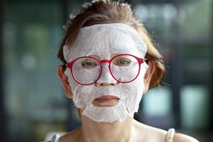 face of woman making face skin tretment masking