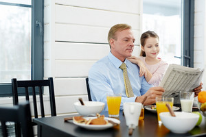 Fair-haired middle-aged man and his pretty little daughter wrapped up in reading newspaper article while having tasty breakfast in dining room, waist-up portrait