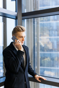 Fair-haired office worker listening to his phone interlocutor with concentration while standing at window of office lobby, waist-up portrait