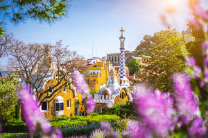 Fairytale house in Park Guell in bright purple lavendel flowers frame. Famous location summer weekend sunset. located on Carmel Hill, Barcelona, Spain