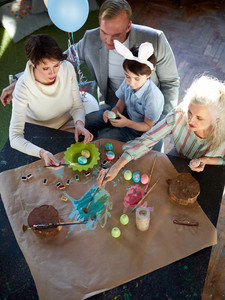 Family of bunny boy, his parents and granny painting Easter symbols