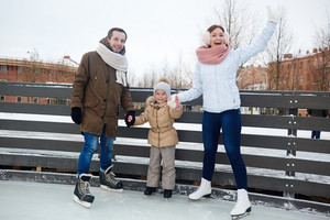 Family of father, mother and daughter on skating rink