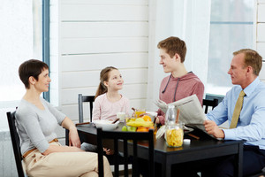 Family of four talking by table after breakfast