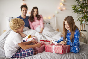 Family spending Christmas morning in the bed