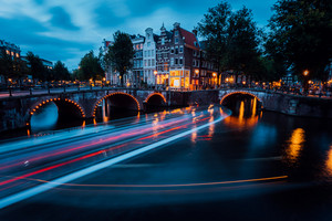 Famous Amsterdam Canal and magic light trails of a Vessel