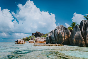 Famous granite boulders in lagoon with shallow ocean water and white cloudscape on amazing Anse Source D'Argent tropical beach, La Digue Seychelles. Luxury exotic travel concept