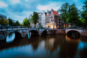 Famous Keizersgracht Emperor's canal in Amsterdam, dutch scenery with illuminated bridge at twilight, Netherlands