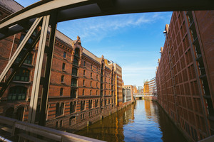 Famous landmark old Speicherstadt in Hamburg, build with red bricks. Bridge in low angle view