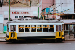 Famous old historic tourist yellow street tram in Lisbon. Famous vintage tourist travel attraction. Colorful architecture city buildings street scene, Portugal