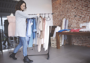 Fashion designer walking with clothes rail