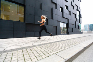 Fast running young woman wearing sports top in modern city environment