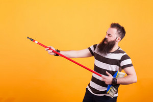 Fat young man picking up a broom as if it were a guitar isolated on white background