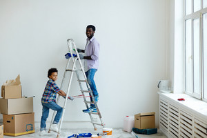 Father and his little son painting walls of new flat