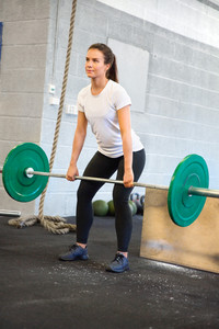 Female Athlete Weightlifting With Barbell In Health Club