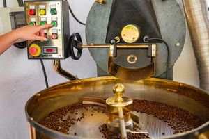 Female Employee Pressing Machinery Button on Coffee Roaster