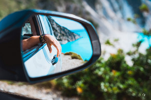 Female hand mirrored in the car side view mirror. Blue mediterranean sea and white rocks in background