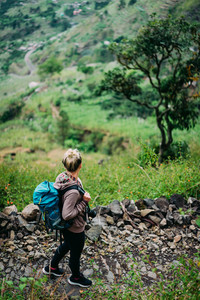 Female hiker with backpack walking down cobbled path to the lush green Paul valley. Santo Antao Cape Verde. Cabo Verde