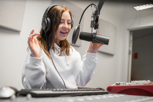Female Host Communicating On Microphone In Radio Studio