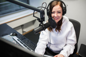 Female Jockey Smiling While Communicating On Microphone In Radio