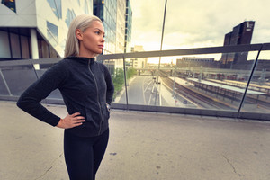 Female Jogger Resting With Hands On Hips After Workout at Sunset