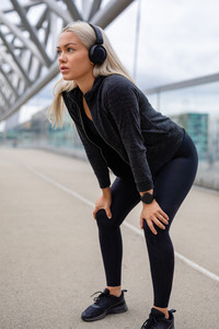 Female Jogger Resting With Hands On Knees After Workout
