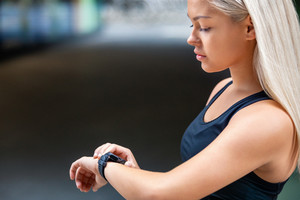 Female Runner Checking Smartwatch After Workout On Road
