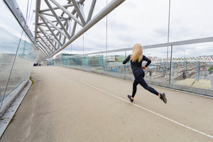 Female runner during fast running exercise in modern city at cloudy day.