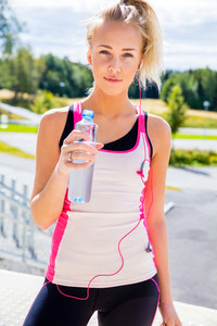 Female Runner In Sportswear Holding Water Bottle On Stairway