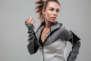 Female runner in warm clothes running in studio and looking back over gray background
