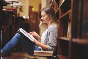 Female student reading and sitting on library floor