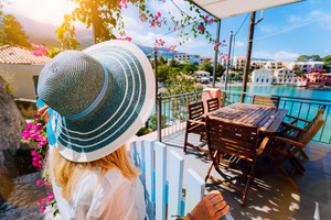 Female tourist in blue sunhat in Assos village in front of cozy veranda door admiring turquoise colored bay of Mediterranean sea and beautiful colorful houses of in Kefalonia, Greece