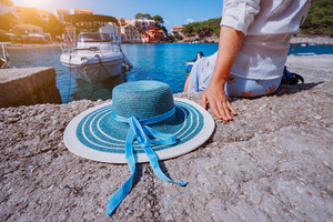 Female tourist sitting on the pier with blau sun hat at her side in Assos village in front of emerald bay of Mediterranean sea and beautiful traditional houses of in Kefalonia, Greece