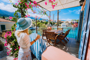 Female tourist with blue hat staying in Assos village in front of cozy veranda and admiring turquoise colored bay of Mediterranean sea and beautiful colorful houses of in Kefalonia, Greece