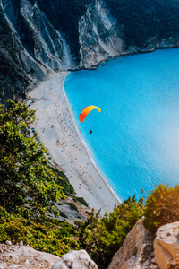 Figure of a parachutist skydiver with orange parachute against a blue lagoon of Myrtos Beach, Kefalonia Island, Greece
