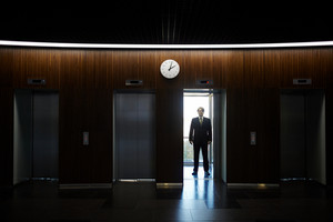 Financial director standing in elevator of office center