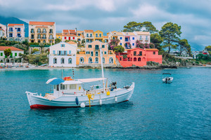 Fishing boat at anchor in blue sea bay of Assos village. Vivid colored houses with clouds in background, Kefalonia island, Greece