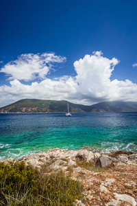 Fiskardo town, crystal clear transparent blue turquoise teal Mediterranean sea water. White yacht in open sea at anchor under amazing white clouds, Kefalonia, Ionian islands, Greece