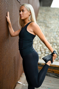 Fit athlete woman stretching after running in modern city environment