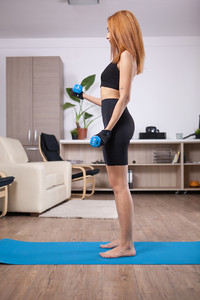 Fit blonde girl doing lateral biceps curls in her home training progam. Black Sportwear.