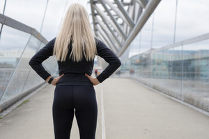 Fit blonde woman runner standing on bridge in modern looking city