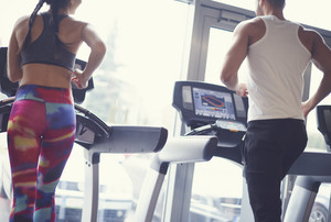 Fit couple exercising on treadmill