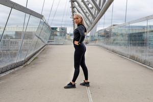Fit Female Beauty in Black Workout Wear Standing At Modern Bridge In City