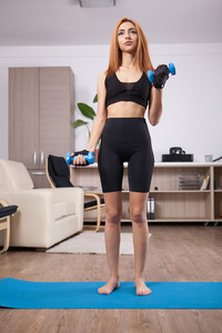 Fit girl doing front biceps curls during her home arms training. Body and spirit training.