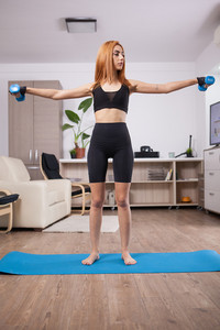 Fit girl doing lateral shoulder rises in her home training progam. Muscle gains.