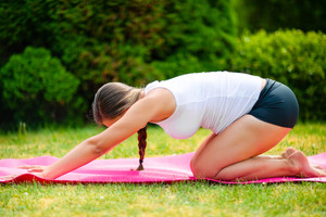 Fit Pregnant Woman Practicing Child's Pose On Mat In Park
