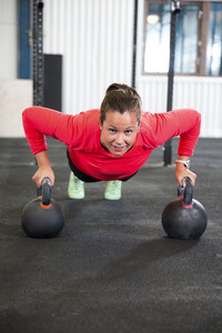 Fit Woman Doing Pushups On Kettlebell In Health Club