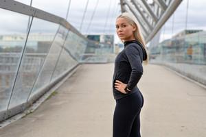Fit Woman in Black Workout Wear Standing At Modern Bridge In City