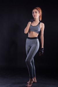Fitness attractive young woman doing lateral poses during studio photoshoot on blackground. Healthy lifestyle.