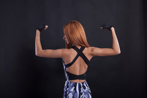 Fitness beautiful girl flexing her back during studio photoshoot. Healthy lifestyle